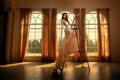 与窗口的美丽的女性画象 库存图片
