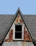 与窗口的老陡峭的屋顶屋顶窗 免版税库存图片