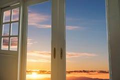 与窗架的现代门有日出天空视图背景 库存照片
