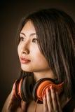 与立体声耳机的年轻亚洲秀丽 库存图片