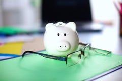 与站立在一台白色和铝计算机的桃红色陶瓷存钱罐的网路银行和投资概念 免版税库存照片