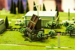 与站立在与绿草和山的领域的蓝色盘区的美好的现代太阳驻地在天际在a下 免版税库存图片