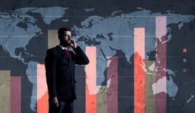 与站立在图的智能手机的商人 世界地图bac 免版税库存图片