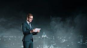 与站立在夜城市backgr的计算机片剂的商人 免版税图库摄影