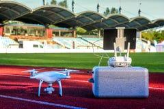 与站立在大体育场内的四台马达和推进器的白色quadcopter 免版税库存照片