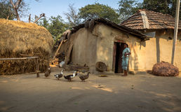 与站立在她的泥房子前面的一名部族妇女的印地安乡村场面 免版税库存图片
