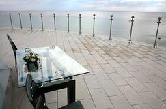 与站立在室外terrase的椅子的图片桌俯视海和多云天空 库存图片