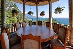与站立在放松的一个眺望台的椅子的一张巨型的圆的木桌与与花和a的垂悬的花盆 免版税库存照片