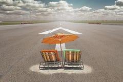与站立在机场跑道的遮阳伞的Sunbeds 免版税库存图片