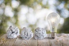 与站立在桌上的一个被弄皱的办公室纸和电灯泡的好主意 库存照片