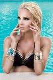 与站立在水池的湿金发的美好的肉欲的妇女模型在比基尼泳装穿戴了 免版税图库摄影