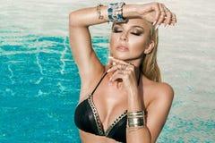 与站立在水池的湿金发的美好的肉欲的妇女模型在比基尼泳装穿戴了 库存图片
