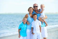 与站立在海滩的孩子的愉快的家庭 库存图片