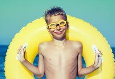 与站立在海滩的游泳者风镜的滑稽的chilld 免版税库存照片