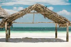 与站立在海洋附近的棚子的白色含沙热带海滩 库存图片