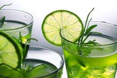 与站立在玻璃的石灰和迷迭香的三个绿色鸡尾酒在演播室,灰色背景 免版税库存照片