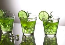 与站立在玻璃的石灰和迷迭香的三个绿色鸡尾酒在演播室,灰色背景 库存照片