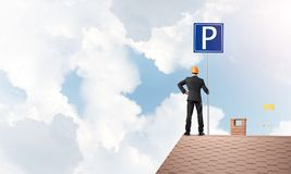 与站立在砖屋顶的停车处标志的年轻商人 混合画法 库存照片
