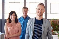 与站立在背景中的工作同事的微笑的年轻商人 库存照片