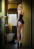 与站立在门框的黑束腰的有吸引力的公平的头发模型 塑造一名肉欲的妇女的画象,背面图,户内射击了 免版税图库摄影