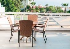 与站立在露天大阳台的四把椅子的表 库存照片