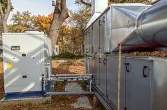 与站立大凝聚的单位的灰色商业透气单位室外在下落的叶子报道的地面上 免版税库存图片