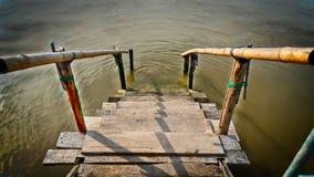 与竹扶手栏杆的小木板条楼梯向海 图库摄影