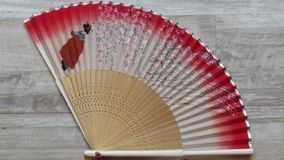 与竹框架的日本红色和白色柔滑的夫人` s爱好者 免版税图库摄影