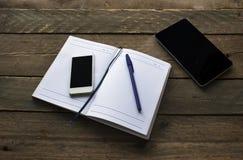 与笔、电话和片剂的笔记薄在木桌上 图库摄影