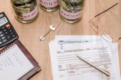 与笔、计算器和美元的报税表1040 库存图片