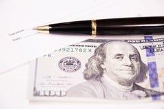 与笔和一一百美元的署名形式 报名参加工商业票据 免版税图库摄影