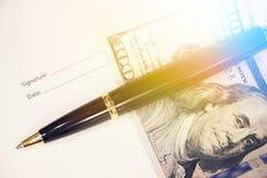 与笔和一一百美元的署名形式 报名参加工商业票据 免版税库存照片