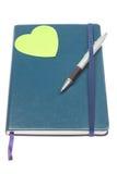 与笔和一个绿色重点的闭合的笔记本。 免版税库存照片