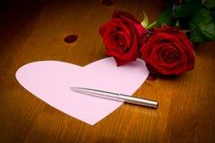 与笔和两朵玫瑰的桃红色心脏笔记 库存照片