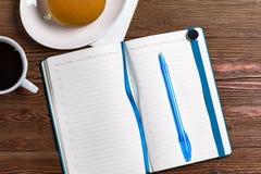 与笔和咖啡的日志 免版税库存图片