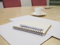 与笔和咖啡,业务会议室的空白的笔记本 免版税库存图片