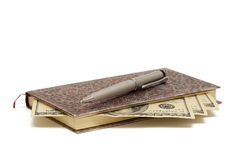 与笔和现金的笔记薄 免版税库存照片