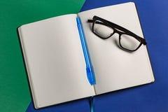 与笔和玻璃的日志 免版税库存图片