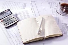 与笔和计算器的日志 免版税图库摄影