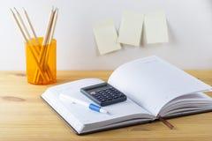与笔容器有铅笔的,计算器的笔记薄在一张木桌上 在桌附近的墙壁上胶合了笔记的纸 图库摄影