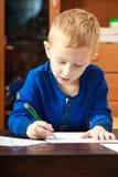 与笔文字的白肤金发的男孩儿童孩子在纸。在家。 免版税库存图片