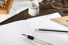 与笔的一个笔杆,一支简单的铅笔、直尺、算盘和玻璃在一个开放笔记本说谎 减速火箭的风格化照片 看法为 免版税图库摄影