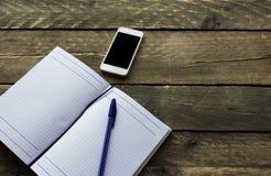 与笔的在木桌上的笔记薄和电话 免版税库存照片