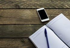 与笔的在老木桌上的笔记薄和电话 免版税库存图片
