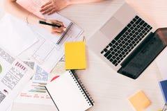 与笔的女实业家文字在桌面的工作场所与膝上型计算机 免版税库存照片