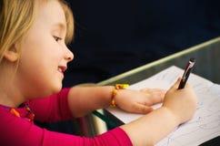 与笔的小女孩图画 免版税库存照片