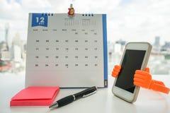 与笔的柱子在日历背景的提示的 库存照片
