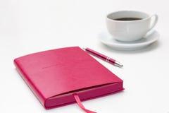 与笔的桃红色日志和一杯在白色的无奶咖啡 免版税库存图片