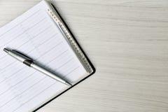 与笔的电话簿在白色桌上 免版税库存照片