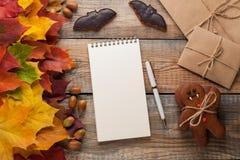 与笔的空白的白色在老笔记薄在秋叶背景和糖果在以南瓜的形式万圣夜和棒求爱 库存图片